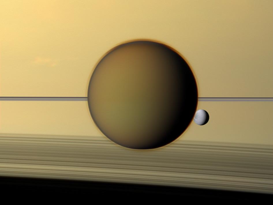 As nuvens de Titã não entregam nada; veja Saturno ao fundo. A lua cinzenta menor é Dione.